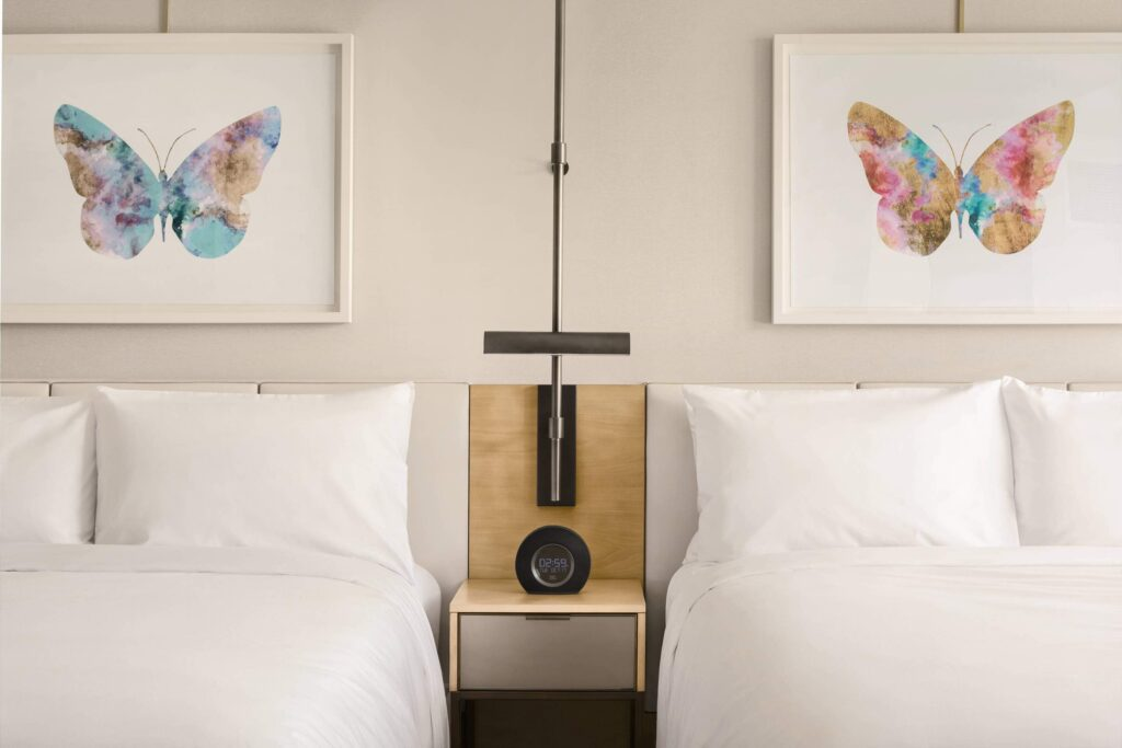 JW Parq Hotel luxury Vancouver bhotels bedroom with two beds and paintings